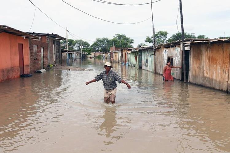 Un poblador trata de cruzar una calle inundada, en la región de Piura, costa norte de Perú. (Foto Prensa Libre: EFE/Elías Agustín)