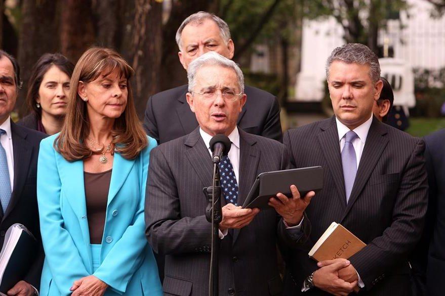 El expresidente y senador colombiano Álvaro Uribe (centro) habla con la Prensa luego de su encuentro con el presidente Santos. (Foto Prensa Libre: EFE).