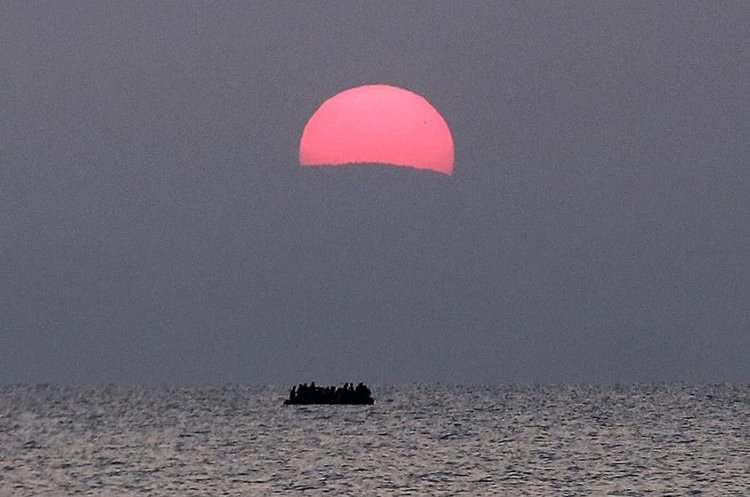A dinghy with migrants sails under a rising sun a few miles off a coast of the southeastern island of Kos, Tuesday, Aug. 11, 2015. Fights broke out among migrants on the Greek island of Kos Tuesday, where overwhelmed authorities are struggling to contain increasing numbers of people arriving clandestinely on rubber dinghies from the nearby Turkish shore.  (AP Photo/Yorgos Karahalis)