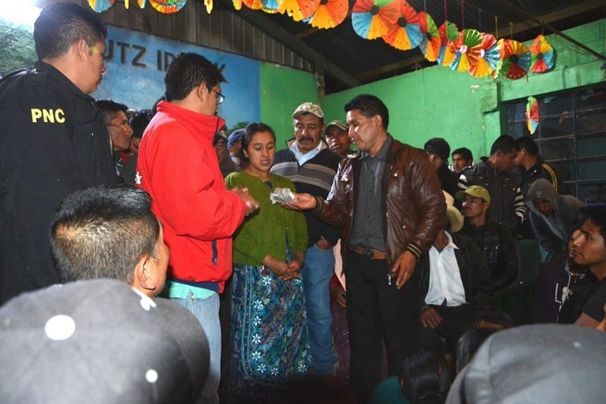 Uno de los sujetos sindicado de ser estafador devuelve dinero a vecinos de Santa Lucia Utatlán. (Foto Prensa Libre: Édgar René Sáenz)