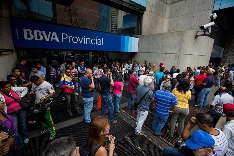 Cientos de personas esperan frente a un banco para cambiar billetes. (Foto PL: EFE)