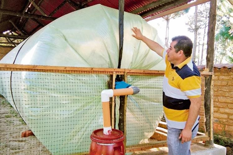 Bayron Velásquez, encargado del proyecto, muestra uno de los tres reservorios de biogás. (Foto Prensa Libre: César Peérez)