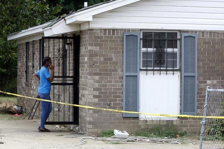 Una mujer observa la vivienda donde ocurrió la tragedia que acabó con varios integrantes de la familia. (Foto Prensa Libre: AP).