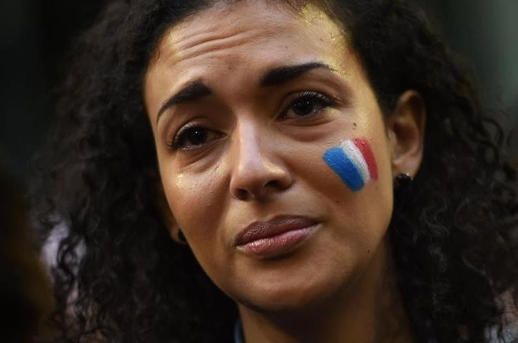 A woman weeps at a vigil held by the local French community in Sydney on November 14, 2015, as Australians express their solidarity with France following a spate of coordinated attacks that left 128 dead and 180 injured in Paris late on November 13. Both the Opera House and the Sydney Town Hall were bathed in the French colours and New South Wales state Premier Mike Baird said he had also asked for a French flag to fly over the city