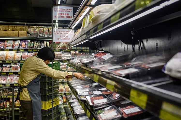 Un empleado de un supermercado en Hong Kong retira productos de estantes, luego del escándalo sobre carne posiblemente contaminada procedente de Brasil. (Foto AFP)