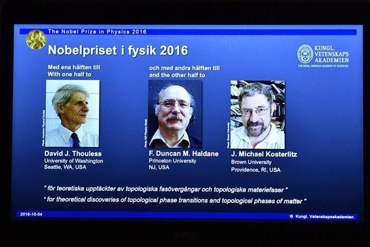 Imagen de una pantalla en la Academia de Ciencias de Estocolmo, Suecia, que muestra a los científicos británicos David Thouless, Duncan Haldane y Michael Kosterlitz. (Foto Prensa Libre: EFE)