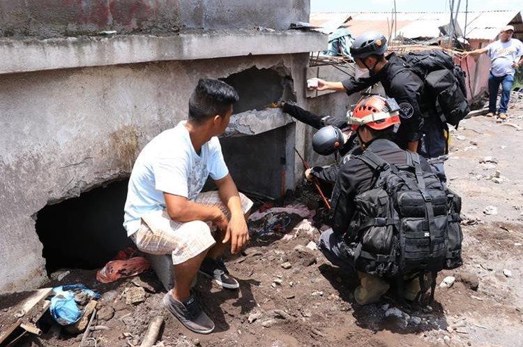 Socorristas junto con un sobreviviente buscan restos de fallecidos en una vivienda. (Foto Prensa Libre: Enrique Paredes)