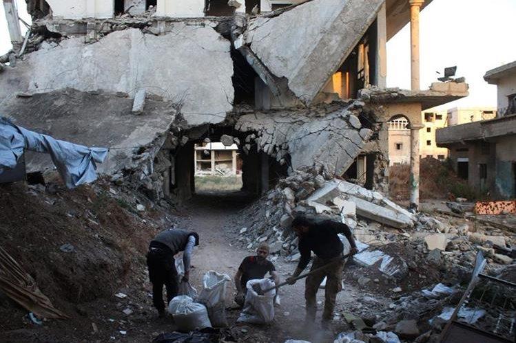 Rebeldes llenan bolsas con restos de edificios destruidos por los bombardeos del regimen. (Foto Prensa Libre: AFP).