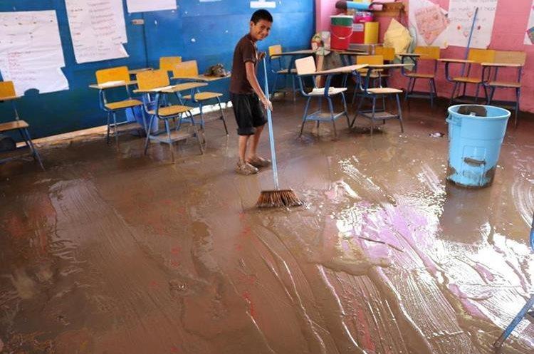 Un estudiante ayuda a los maestros a limpiar uno de los salones de clases de la Escuela San Antonio Chiquito.(Foto Prensa Libre: Héctor Cordero)