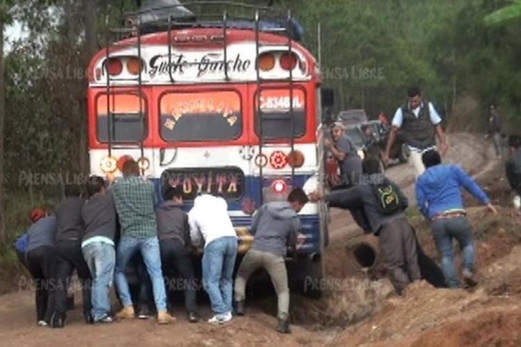 Pasajeros empujan un bus que se atascó en la ruta entre Chuiquisis y Santa Cruz del Quiché. (Foto Prensa Libre: Héctor Cordero).