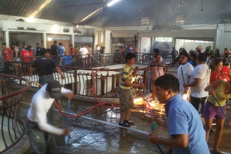 Vendedores limpian el área donde ocurrió el incendio. (Foto Prensa Libre: Cristian Icó Soto)