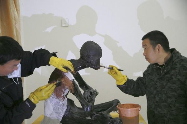 Los expertos le aplican laca sobre el cuerpo momificado de Fu Hou. (AP).