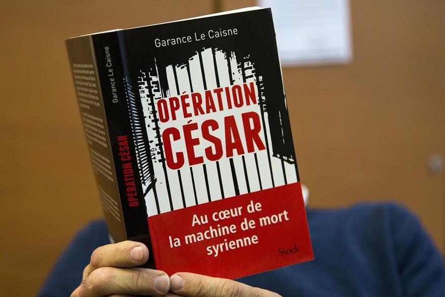 """Un hombre lee el libro, """"Operación César, en el corazón de la máquina siria de la muerte"""", que detalla las fotografías de torturas y masacres cometidas, supuestamente por el regimen de Bashar al Asad. (Foto Prensa Libre: AFP)."""