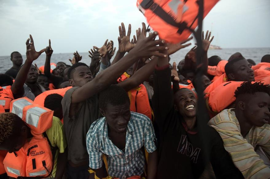 Varios migrantes se abalanzan para recibir un chaleco salvavidas. (Foto Prensa Libre: AFP).
