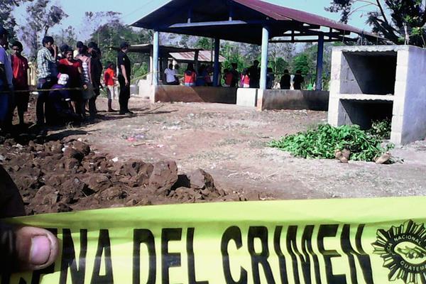 Pobladores de  la aldea La Montaña, Retalhuleu, observan el lugar donde fue hallado el cadáver de una mujer, en el cementerio local. (Foto Prensa Libre: Jorge Tizol)