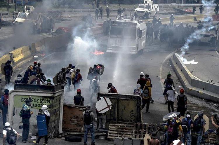 Opositores a Maduro se resguardaban con barricadas, para evitar ser alcanzados por gases lacrimógenos y bombas de goma.