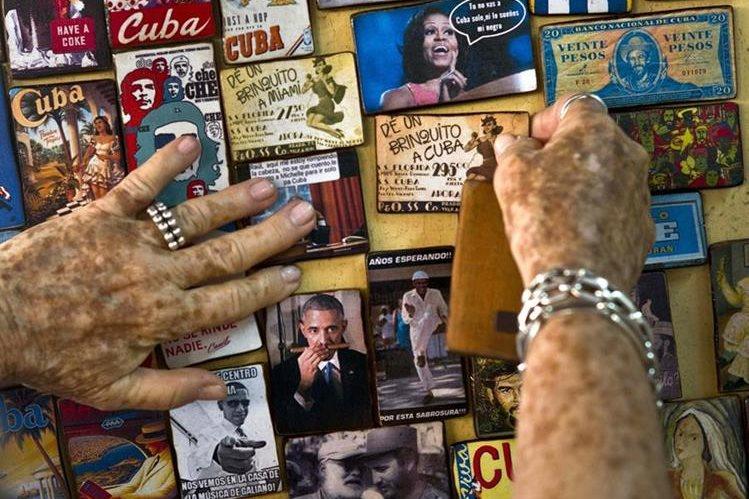 Una cubana muestra varios artículos promocionales a la venta alusivos a la visita de Obama. (Foto Prensa Libre: AP).