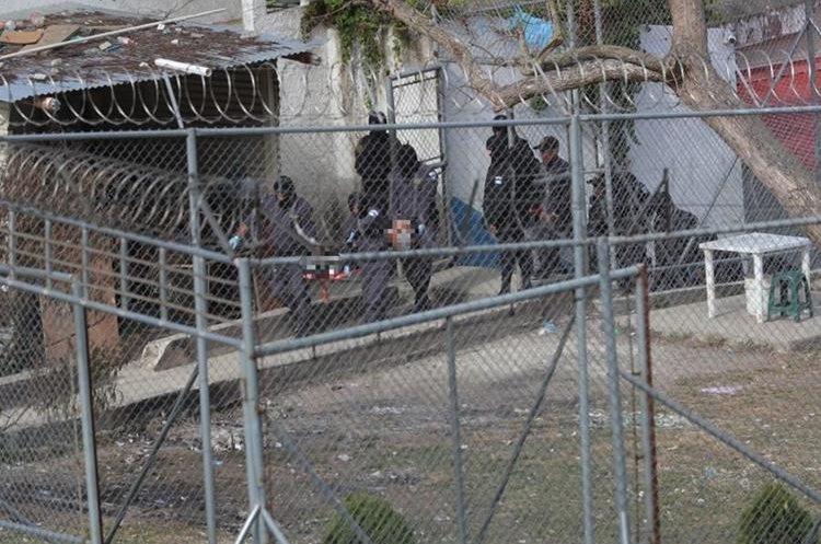 Guardias penitenciarios retiran cuerpos de pandilleros asesinados. (Foto Prensa Libre: Hemeroteca)