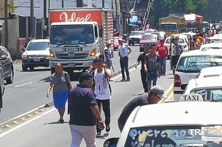 Las personas caminan sobre la vía del Transmetro para llegar a sus labores.
