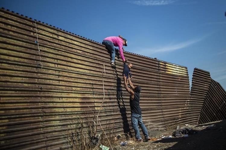 Migrantes intentan cruzar por valla fronteriza en Tijuana, México. (Foto Prensa Libre: AFP)