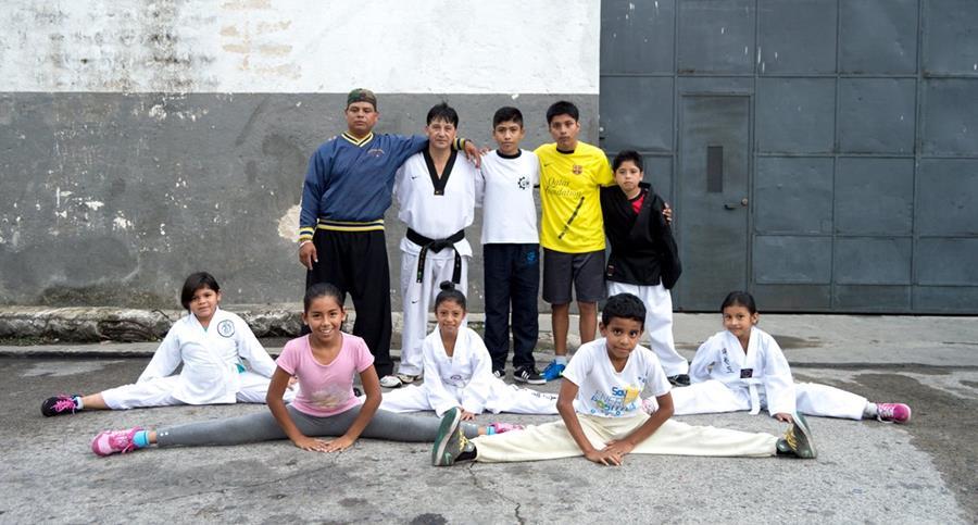 Los instructores Alfonso Gómez, con uniforme blanco y cinta negra, y Víctor Reyes —con sudadero azul— posan con algunos de sus discípulos. Foto Prensa Libre: Roberto Villalobos Viato.