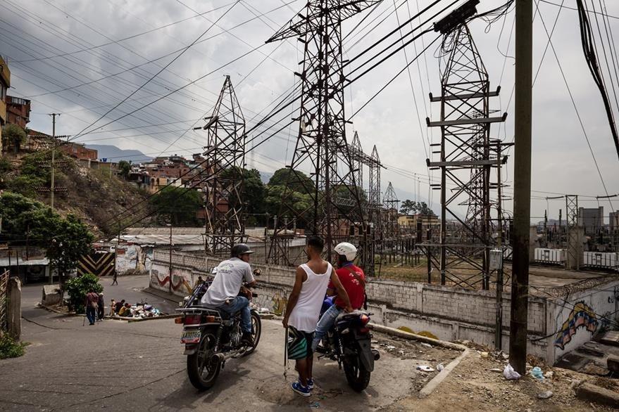 Un grupo de personas habla frente a una estación eléctrica en el sector Catia en la ciudad de Caracas (Venezuela), el país enfrenta una grave crisis energética. (Foto Prensa Libre: EFE).