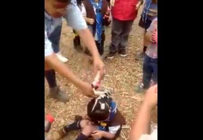 Captura del video donde una mujer adulta vacía una botella de refresco a la pequeña quien llora desesperadamente. (Foto: Faceook).