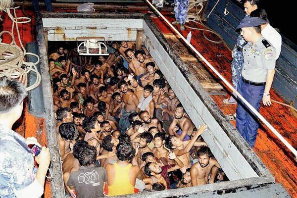 Varios agentes de la Policía birmana  observan a un grupo de inmigrantes en una embarcación en Rakhine, Birmania,  la mayoría de ellos procedentes de Bangladés. (Foto Prensa Libre:EFE)