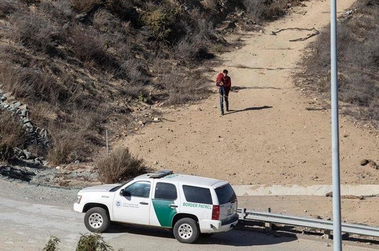 FOTO1: Un migrantes y su hijo parecen acudir a una patrulla fronteriza en Tijuana, México. (Foto Prensa Libre: AFP)