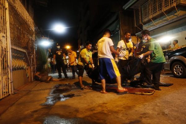 Policías trasladan a una de las víctimas asesinadas en Manila,Filipinas.(Foto Prensa Libre:EFE)