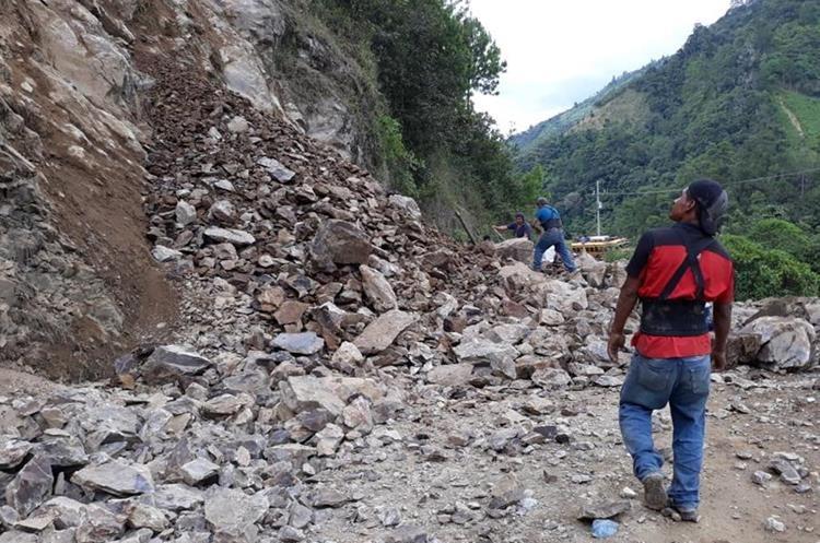 Algunos vecinos de Chajul, Quiché, tratan de caminar entre las enormes piedras que cayeron y bloquean el paso, para llegar a sus destinos. (Foto Prensa Libre: Héctor Cordero)