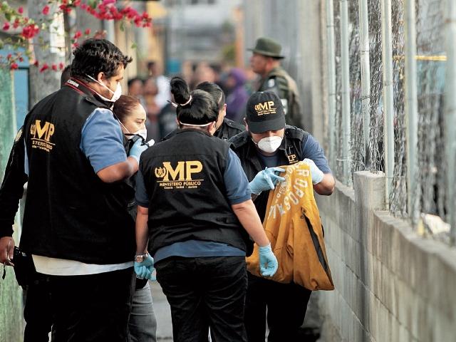 Personal del Ministerio Público revisa una bolsa donde se encontraron partes del cuerpo de una mujer, en la colonia Alameda 2, zona 18. (Foto Prensa Libre: Érick Ávila)
