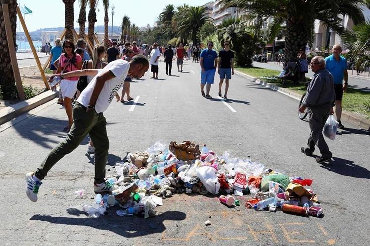 """Un hombre escupe en el lugar donde Mohamed Lahouaiej Bouhlel cayo muerto, abatido por la Policía en Niza. En el área las personas han lanzado basura y escrito la frase """"¡cobarde!"""". (Foto Prensa Libre: AFP)."""