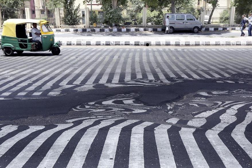 Señales de tránsito pintadas sobre el pavimento aparecen distorsionadas a causa de las altas temperaturas registradas en Nueva Delhi (India). (Foto Prensa Libre: EFE).