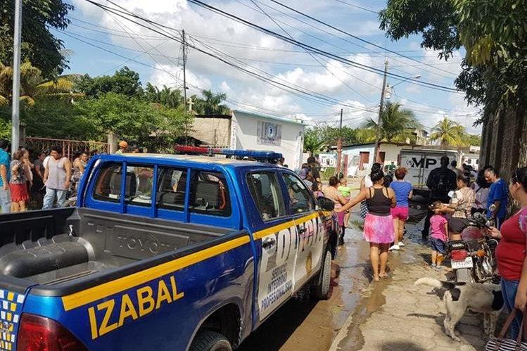 Curiosos permanecen en el lugar donde murió baleado Salvador Díaz Molina, en Puerto Barrios. (Foto Prensa Libre: Dony Stewart).
